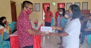 Kepala Desa Komus I, Pirsen Tahulending saat menyerahkan BLT kepada KPM